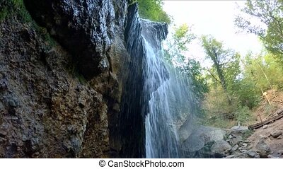 a small waterfall breaks from the stones - A small...