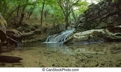 A small waterfall flows from an abandoned stone wall. - The...
