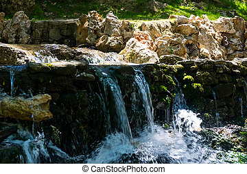 A small waterfall on the river on a sunny day in Rhodes in Greece.