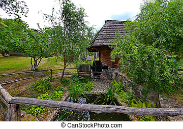 A small well with a wheel under the roof of a wooden house