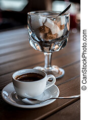 A small white porcelain espresso cup on a saucer with a teaspoon and two pieces of sugar
