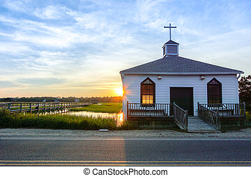 small white wooden chapel on the water on the coast during a colorful summer sunset with illuminated golden windows and a setting sun under a blue sky with soft clouds