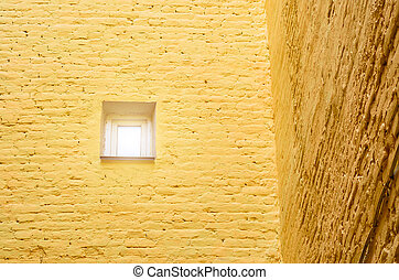 A small window in the brick wall. Corner of the house. Concept minimalism.
