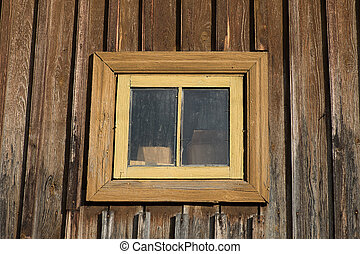 A small window on the wall of the old rustic house