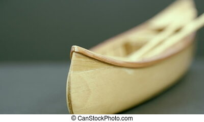 A small wooden canoe boat on the table