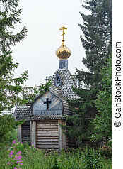 a small wooden chapel in the forest with a golden dome on the shore of Lake Zyuratkul, Ural, Russia