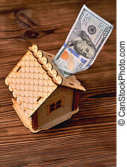 A small wooden house-piggy bank and a money bill of 100 dollars on a wooden brown background