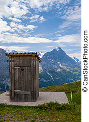 A small wooden outhouse standing high in the Swiss alps