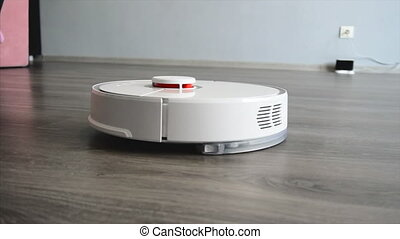 A smart robotic vacuum cleaner cleans the floor in the...