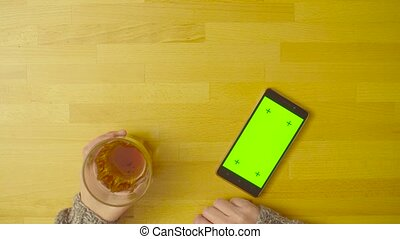 A smartphone with green screen on the table