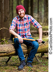 a smiling bearded lumberjack in a hat and shirt with an ax sits on a log in the woods