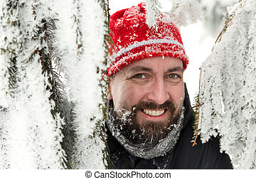 smiling bearded man between snowy fir needles