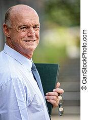 A smiling businessman holding a folder