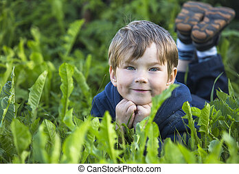 A smiling child lies in the grass at the park.