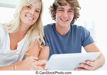 A smiling couple holding a tablet and looking at the camera