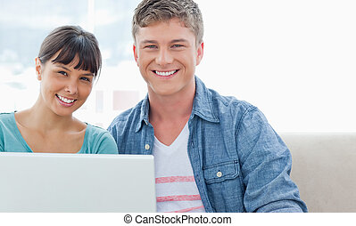 A smiling couple look into the camera as they hold a laptop in their hands