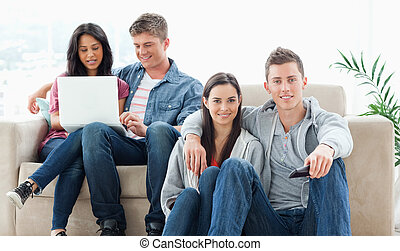 A smiling couple on the ground with a tv remote while another group sit on the couch together with a laptop