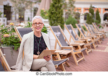 a smiling elegant woman having a rest on the street with beautiful nature