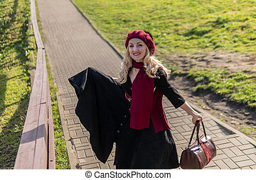 A smiling girl walks up the stairs in burgundy palla and biret, with a kind look in black clothes, in the fall against the background of a pond there are blue clouds.