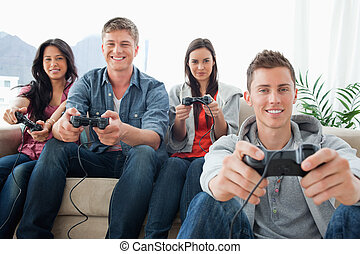 A smiling group of friends playing games together while sitting on the couch as one man sits on the ground as they all look into the camera