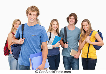 A smiling group of students all looking at the camera while one man stands in front of the rest of the group