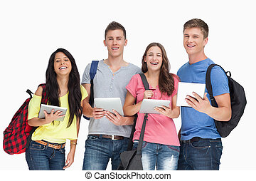 A smiling group of students with backpacks and tablets as they look into the camera
