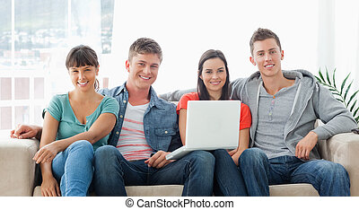 A smiling group sit on the couch as they look at the camera while they hold a laptop in front of them