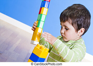 A smiling little boy is building a toy block. Wooden room