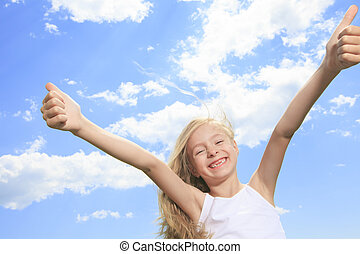 A smiling little girl in white blank t-shirt showing thumbs up o