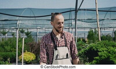A smiling man is a gardener dressed in an apron with garden tools. Agricultural greenhouse with a lot of beautiful plants.