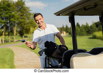 A smiling man pulls out of a bag with sticks, a golf club. Bag lies on the luggage compartment of the golf cart