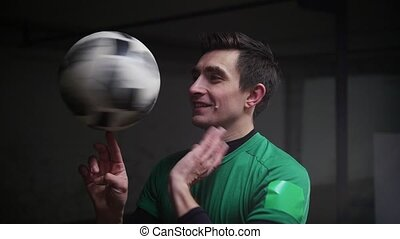 A smiling man spinning the football ball on his finger. Mid...