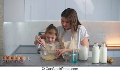 A smiling mother helps her daughter learn how to make a pie. Teach a little girl home help.