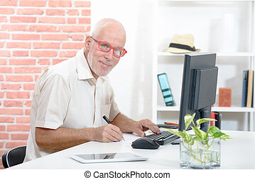 smiling senior businessman with red glasses in his office