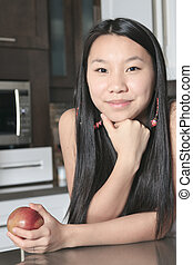 smiling teenager girl with apple in kitchen
