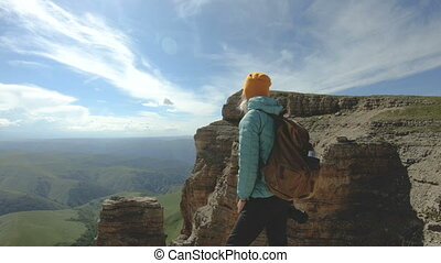 A smiling traveler girl with a backpack and wearing...