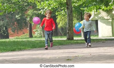 A smiling two little sisters with balloons running in the park, Slow motion