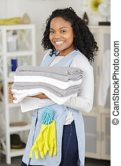 a smiling woman holding towels