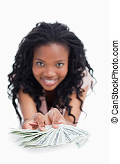 A smiling woman is holding American dollars out in front of her