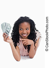 A smiling woman is pointing at American dollars in her hand