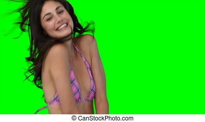 A smiling woman jumping up and down in a bikini