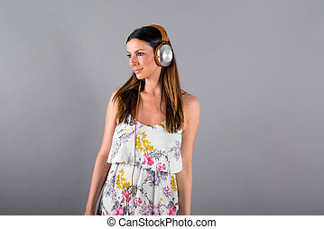 A smiling woman listening to music with a pair of headphones