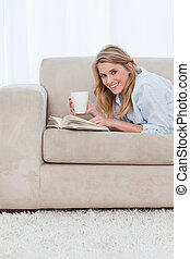 A smiling woman with a book is looking at the camera and holding a cup of coffee