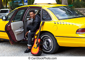 A smiling young man in car with opened door of yellow car, looking and smiling, with left leg outside, near guitar.