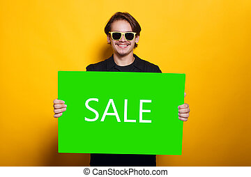 A smiling young man in sun glasses, holding in hands a green banner with inscription Sale, isolated on a yellow background.