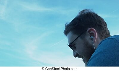 A smiling young man with headphones and glasses looking at the sky on the plane. Portrait of a handsome young man looking at a plane in the sky. The plane leaves a trail.