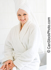 a smiling young woman in bathrobe with towel on her head