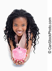 A smiling young woman is looking at the camera and holding a piggy bank in her hands against a white background