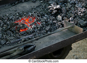 The tools of a medieval blacksmith next to hot embers.