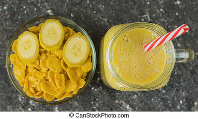 A smoothie of mango, banana, cereal and honey on the dark wooden table in a glass beaker. The view from the top.